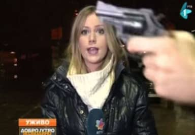 Man Waves Gun In Front Of Live TV Reporter, She Just Carries On Anyway
