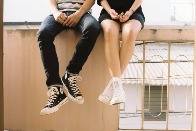 Man and woman sitting on ledge