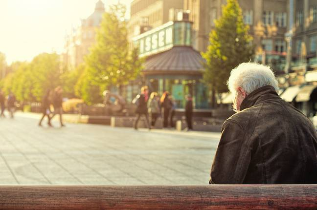 A man sitting on town centre bench