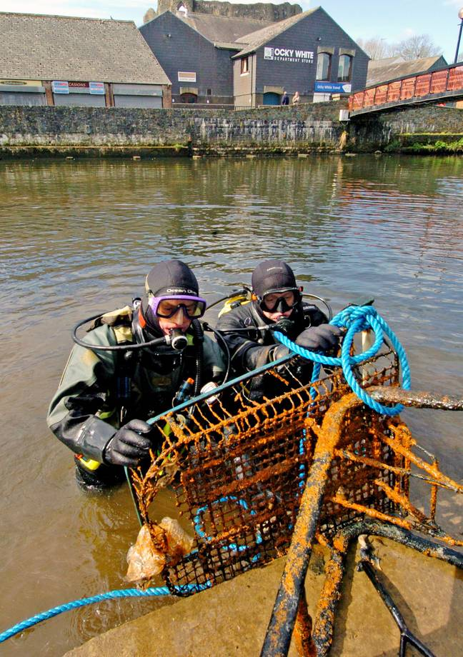 Divers clean shopping trolley out of ocean