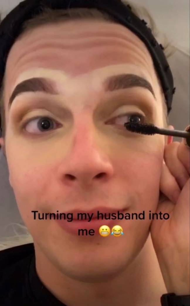 Wife putting makeup on husband to transform him into herself