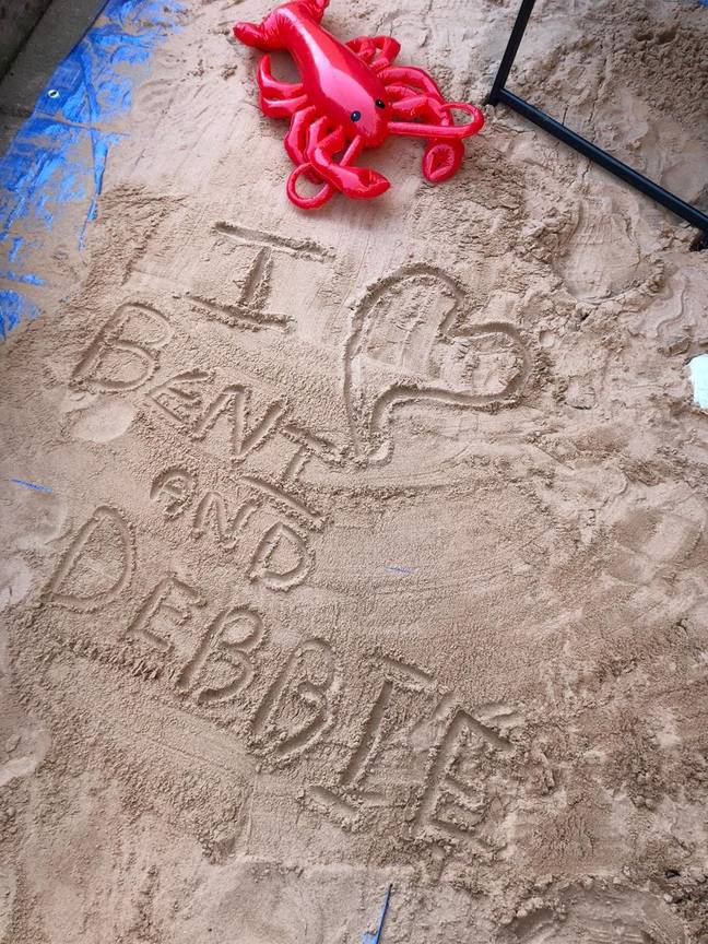 Family draw in the sand on their fake beach in garden