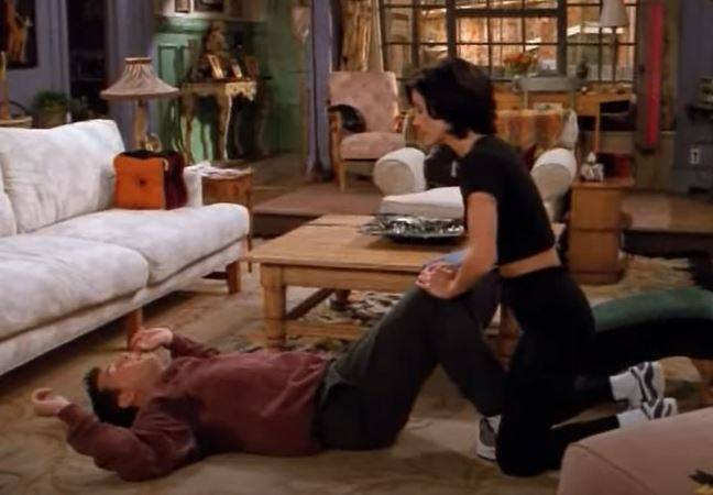 Monica helping Chandler work out