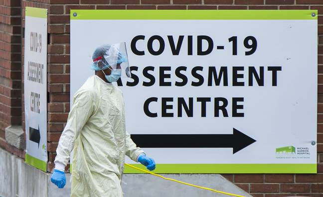 Person wearing PPE by a COVID assessment centre sign (PA)