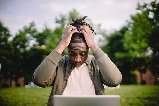 Man on laptop looking stressed