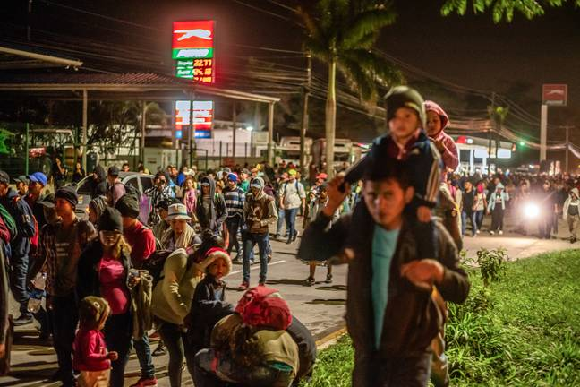 Migrants walk with their children towards the Guatemalan border (PA)
