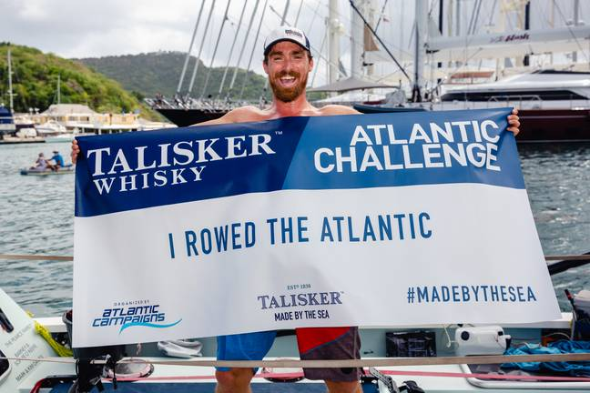 Gareth with 'I rowed the Atlantic' sign