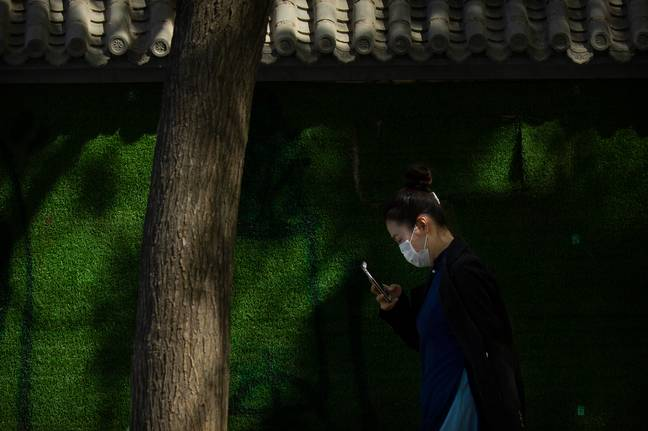 Woman wearing a face mask in Beijing, China. (PA Images)