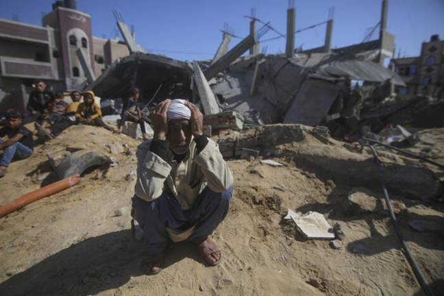 Palestinian man outside rubble of house (PA Images)