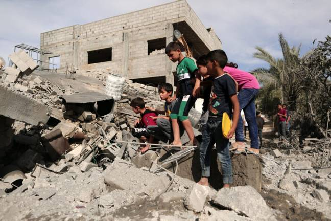 Palestinian children beside houses destroyed during an Israeli airstrike (PA Images)