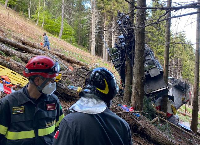 Workers surrounding wreckage of cable car (PA Images)