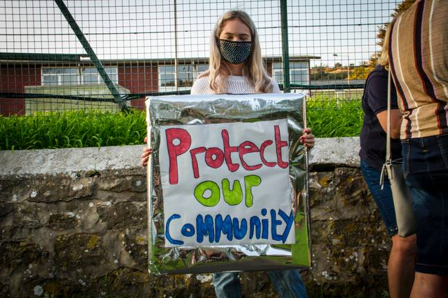 Woman with Protect Our Community sign (Simon Worley)