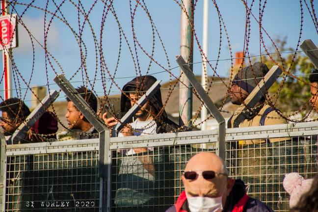People gathered at fence of camp (Simon Worley)