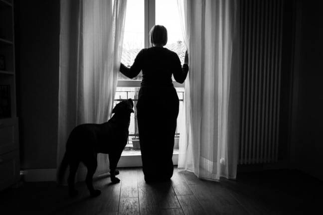Woman looks out of window during pandemic (PA Images)