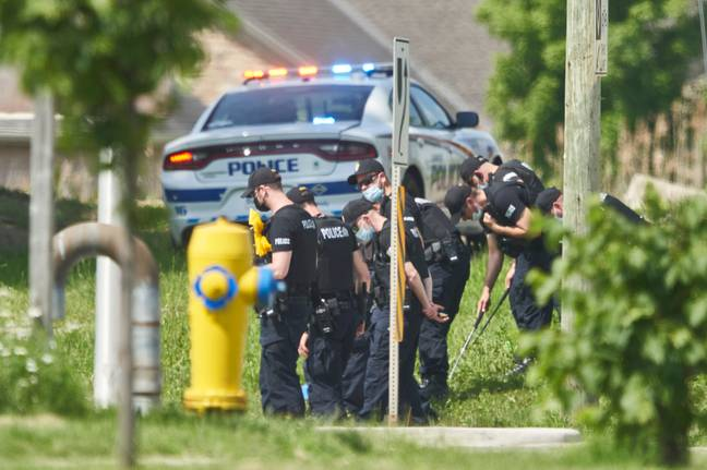 police officers look for evidence at the scene of a car crash in London, Ontario (PA)