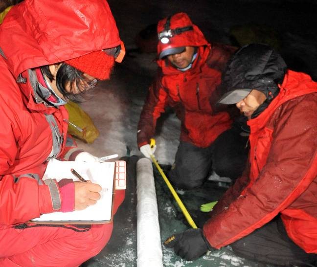 Members of a research team of China's second scientific expedition on the Qinghai-Tibet Plateau measure ice in southwest China. (PA Images)