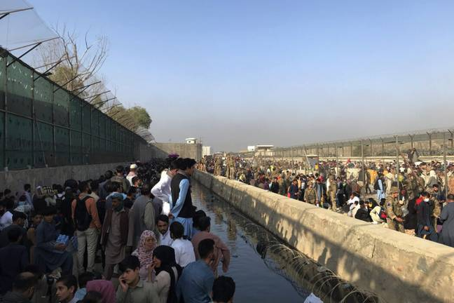 Afghans gather near a gate of Kabul airport (PA)