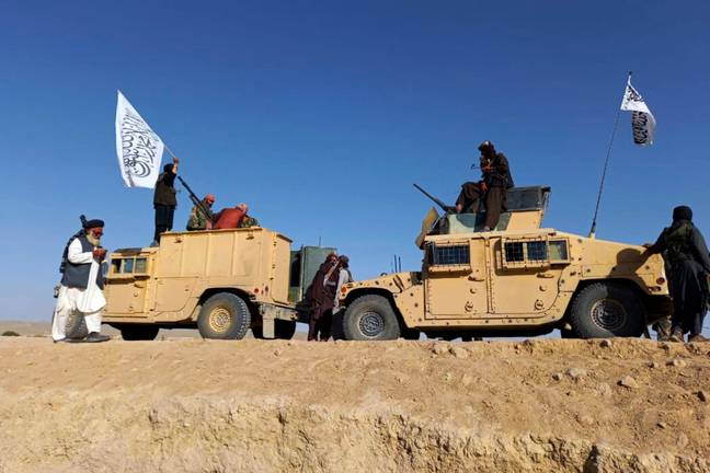 Taliban fighters in possession of military vehicles (PA Images)