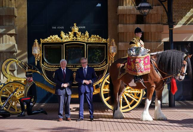 Simon Brooks-Ward, Producer and Director, (right) and Sir Mike Rake, Chairman of the Advisory Committee, pose for a photograph in front of the Diamond Jubilee State Coach, during the media launch for the Queen's Platinum Jubilee celebration at the Royal Mews, Buckingham Palace, London. In 2022 Queen Elizabeth II will become the first British Monarch to celebrate a Platinum Jubilee - seventy years of service - having acceded to the throne on 6th February 1952. Picture date: Tuesday September 21, 2021.