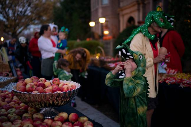 Isaac Webster, 5, bitesinto an apple while going through the treat line with his sister, Meg, 3, his dad and his grandma, Rita McKee, right on Halloween at the Governor's Residence Wednesday, Oct. 31, 2018 in St. Paul, Minn - (PA)
