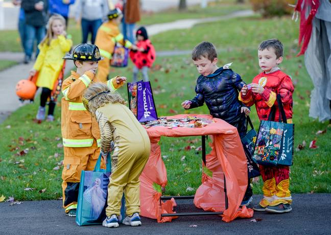 October 31, 2020, St. Charles, Illinois, USA: A group children in costume choose candy from a table placed as the end of a driveway as covid-19 altered how kids performed their annual Halloween Trick or Treating in St. Charles, IL on Saturday, Oct. 31, 2020 -Mark Black/Zuma Press/PA Images