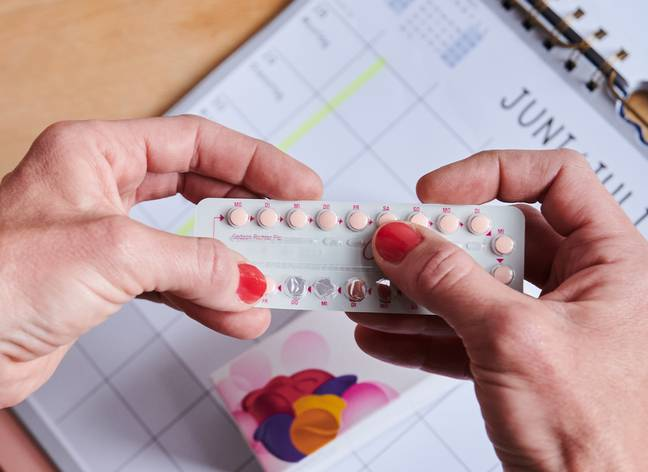25 May 2021, Berlin: Above a calendar, a woman takes the next pill from the monthly pack of the contraceptive pill. The birth control pill went on sale in Germany 60 years ago.- Annette Riedl/DPA/PA Images