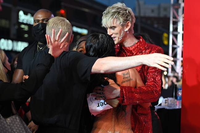 Machine Gun Kelly (red) embraces Megan Fox after an altercation on the red carpet with Conor McGregor (not in frame) at the 2021 MTV Video Music Awards held at the Barclay's Center in Brooklyn, NY on September 12, 2021. -Anthony Behar/SIPA USA/PA Images