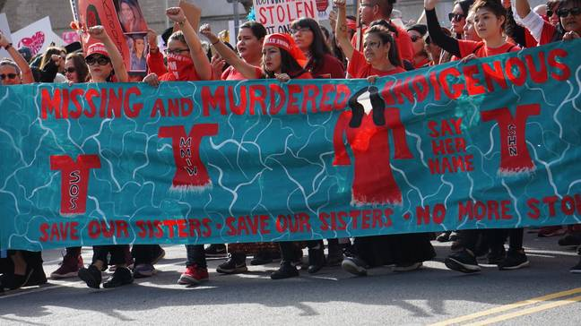 Indigenous or Native American women marching with a banner with fists in air (Alamy)