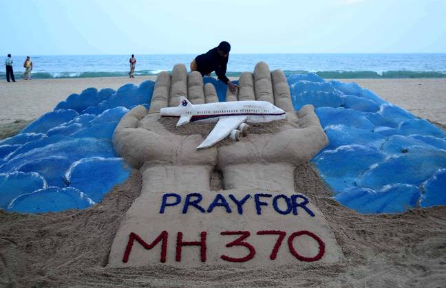 MH370 - Puri, India.  12th Mar, 2014. Sand artist Sudarshan Pattnaik works on a sand sculpture praying for missing Malaysian Airlines flight MH370, on a beach in Puri, India on March 12, 2014. Credit: Stringer / Xinhua / Alamy Live News