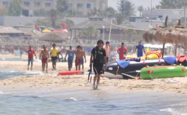ISIS gunman Abu Yahya al-Qayrawani  walking on Sousse beach carrying his gun.