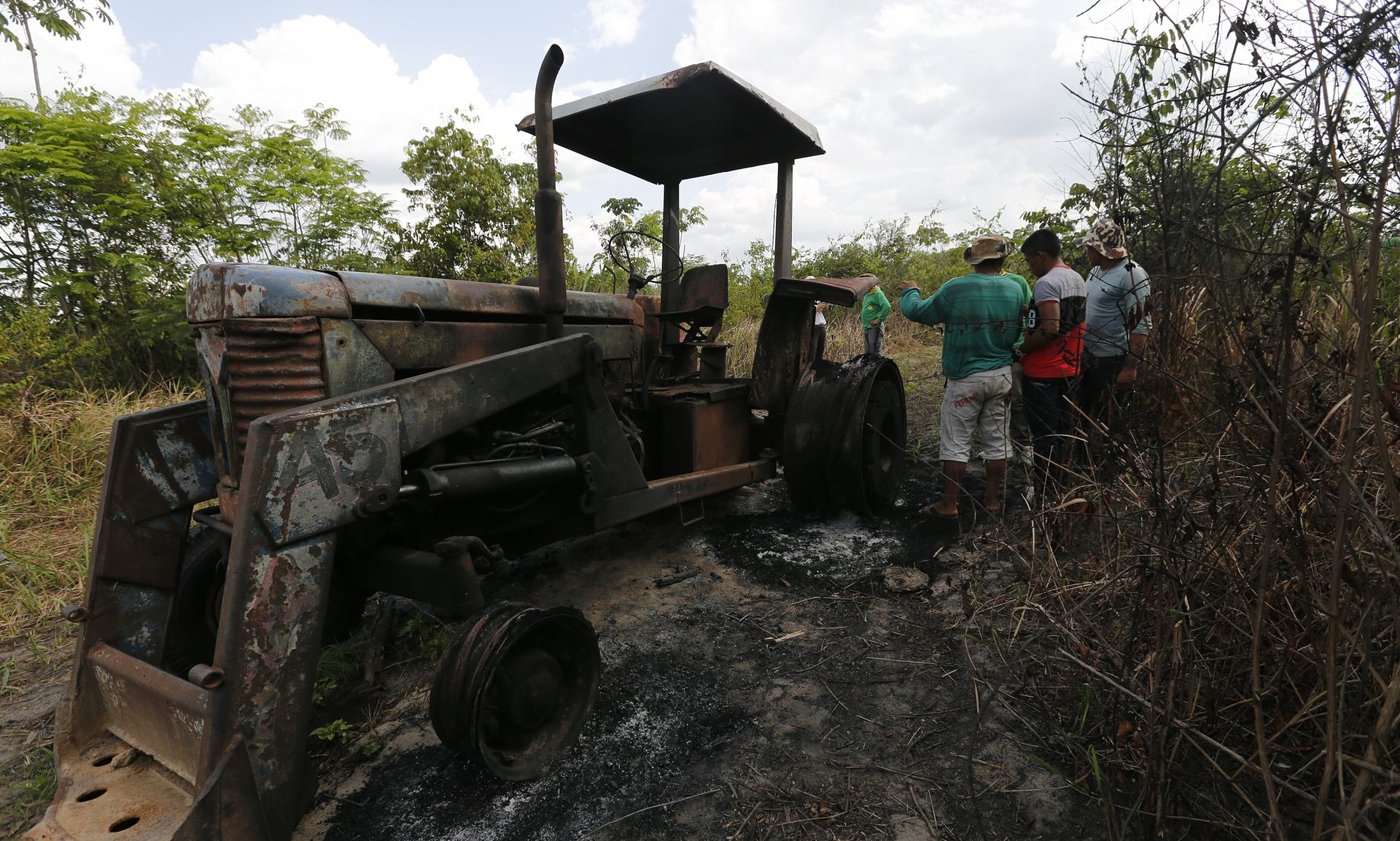 Ka'apor Indians stand next to a logging tractor that they discovered and set on fire inside the indigenous territory one month before. Photograph- Lunae Parracho:Greenpeace