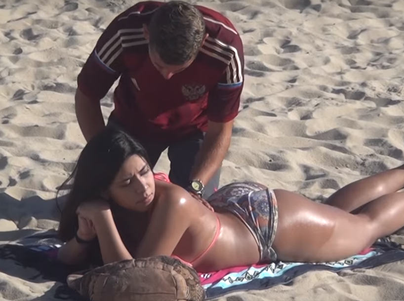 men rub sun cream onto bikini clad girl on beach get big