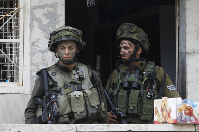 Israeli soldiers stand outside a Palestinian house during a search near the Tel Rumeida settlement in the West Bank city of Hebron, Saturday, Nov. 7, 2015. Three assaults took place Friday in Hebron, the West Bank's largest city, which has been the main area of friction in recent weeks. Hundreds of combat troops guard about 850 Jewish settlers in the center of Hebron where they live amid tens of thousands of Palestinians. (AP Photo/Nasser Shiyoukhi)
