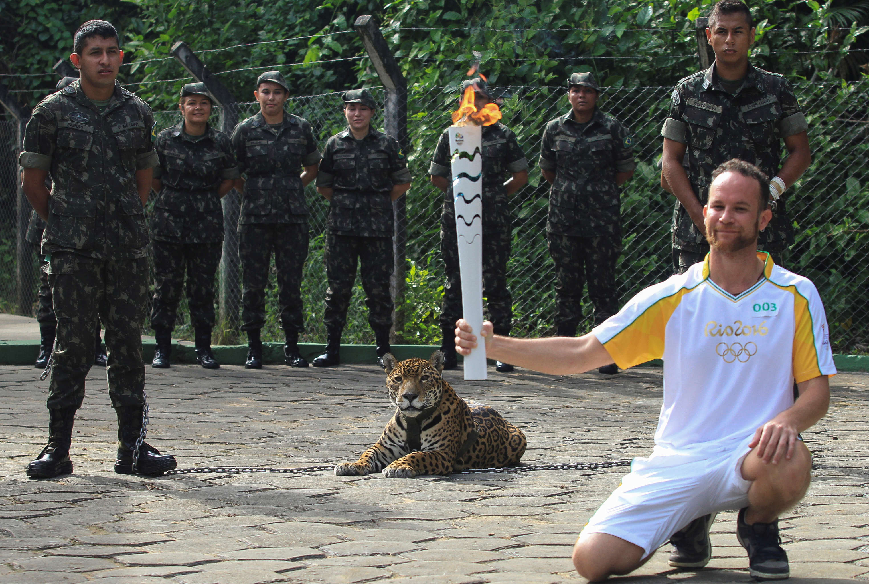 Brazilian physiotherapist Igor Simoes Andrade poses for picture next to jaguar Juma as he takes part in the Olympic Flame torch relay in Manaus