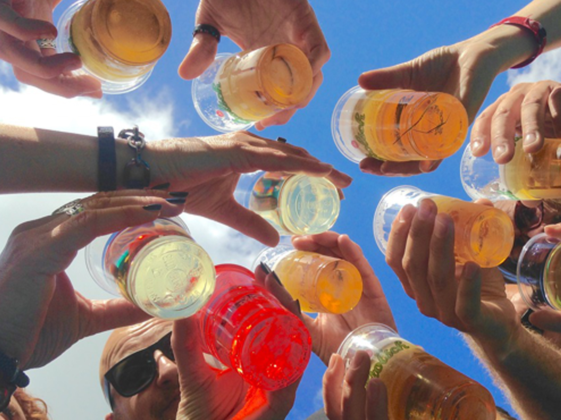 a ground up view of people bringing plastic glasses together for a cheers in the sunshine