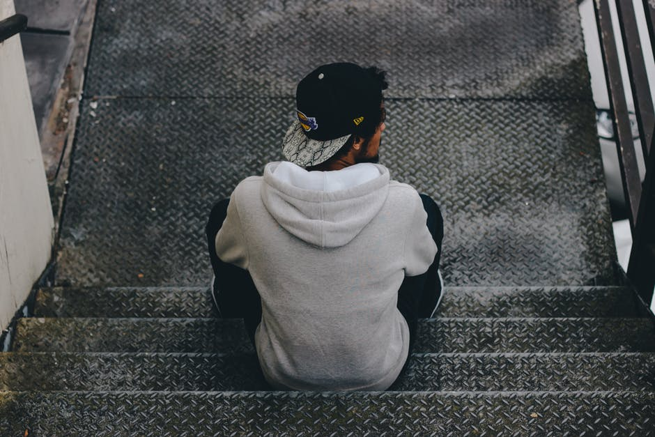 man in hoodie sitting on stairs