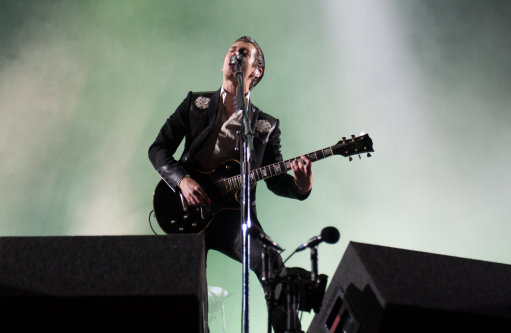 Alex Turner performing on stage with the Arctic Monkeys in his 0more recent Teddy Boy style