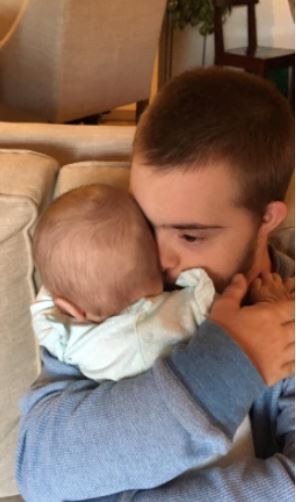 Pic Of Man With Downs Syndrome Holding Baby Goes Viral For All Right Reasons Throop