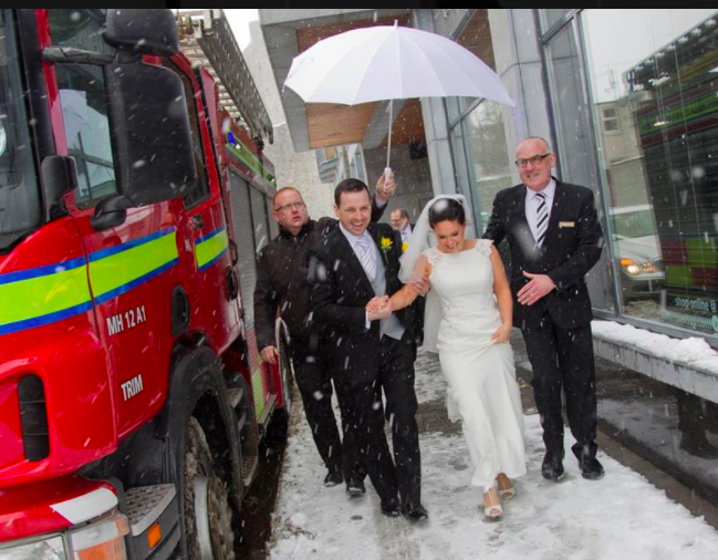 happy married couple walk under an umbrella and past a fire engine in the snow