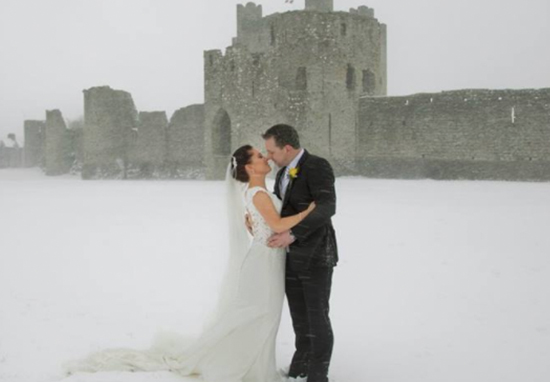 married couple kiss outside Trim Castle Hotel in the snow from the recent Beast from the East storm