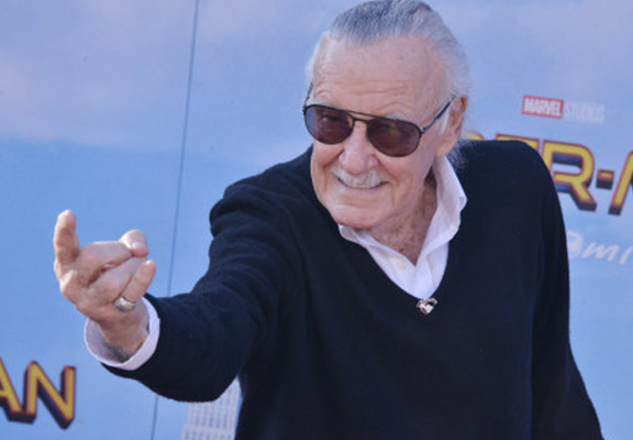 Stan Lee posing on the red carpet at the Spider-Man: Homecoming premiere