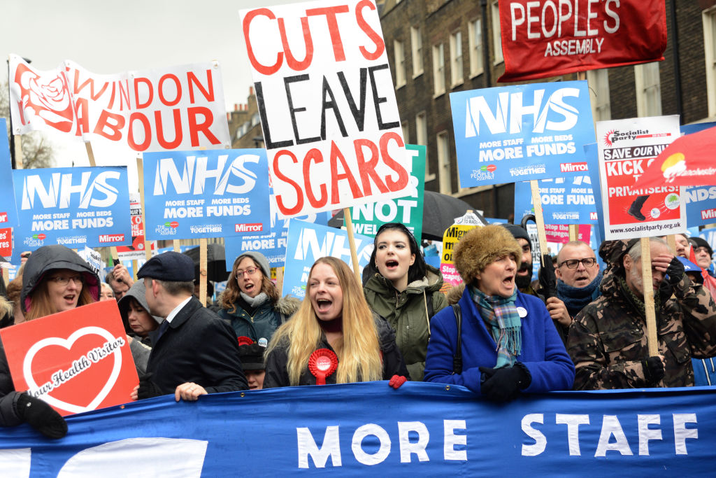 "housand of people marched in London in a protest called ""NHS in crisis - fix it now"" to call for government action to demand the end of NHS crisis and cuts to mental health services."