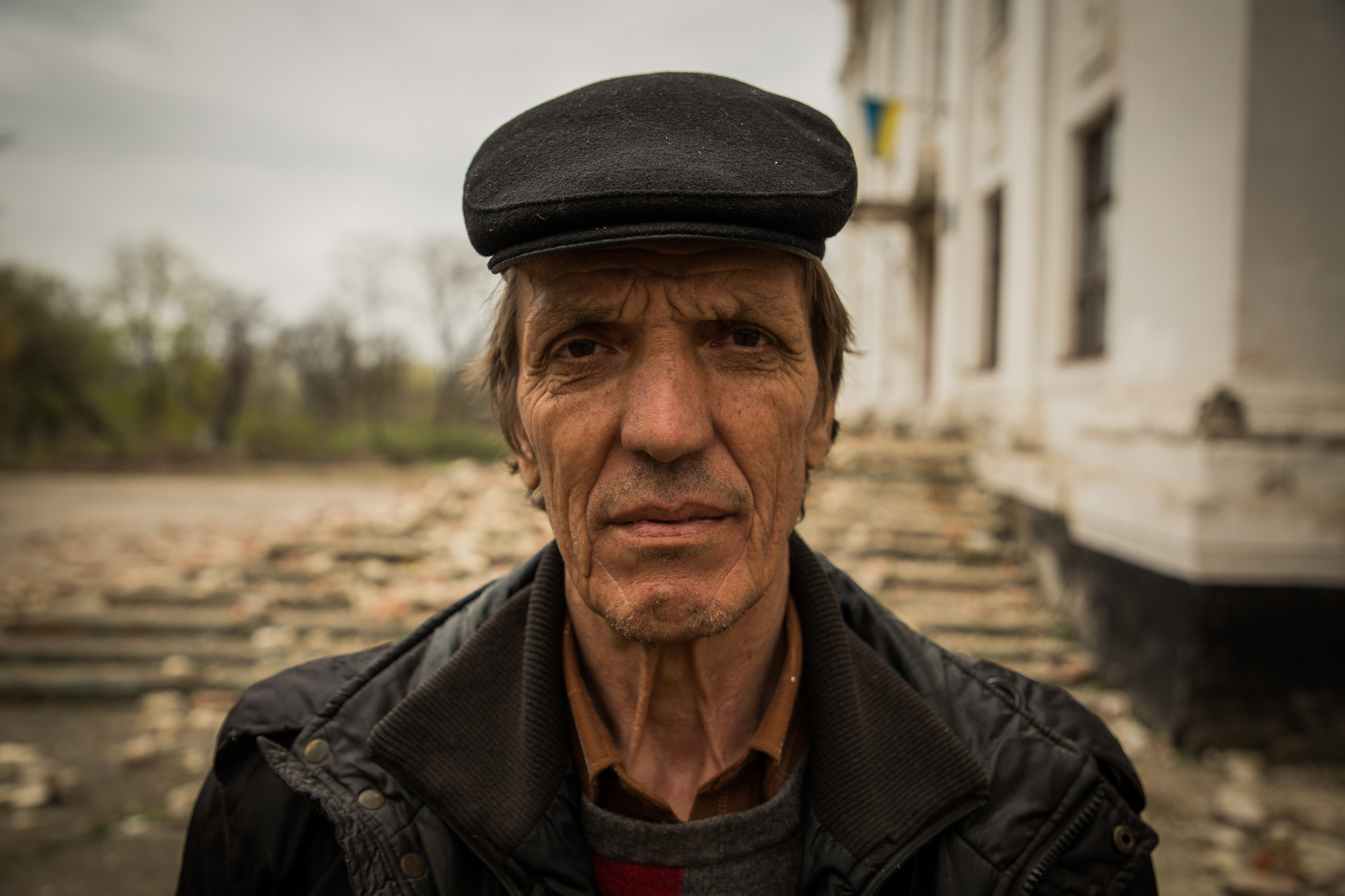 A caretaker stands outside his school in the front line town of Krasnohorivka Eastern Ukraine.