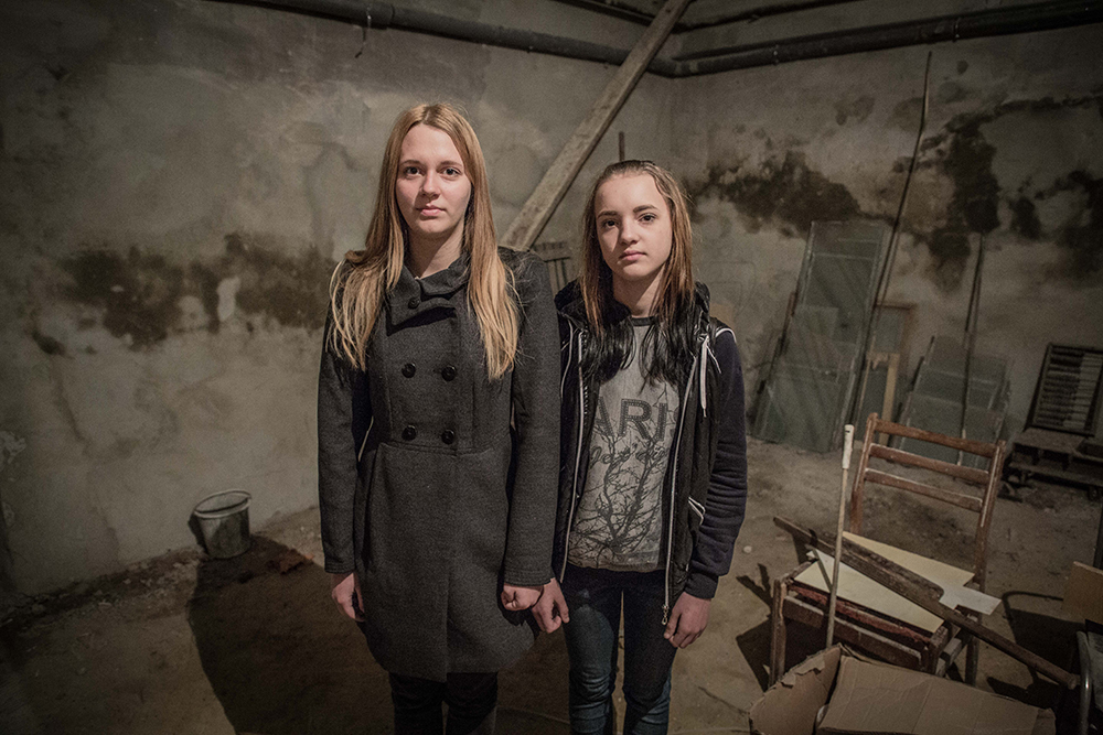 Two girls stand in their schools bomb shelter in Krasnohorivka, Easter Ukraine.
