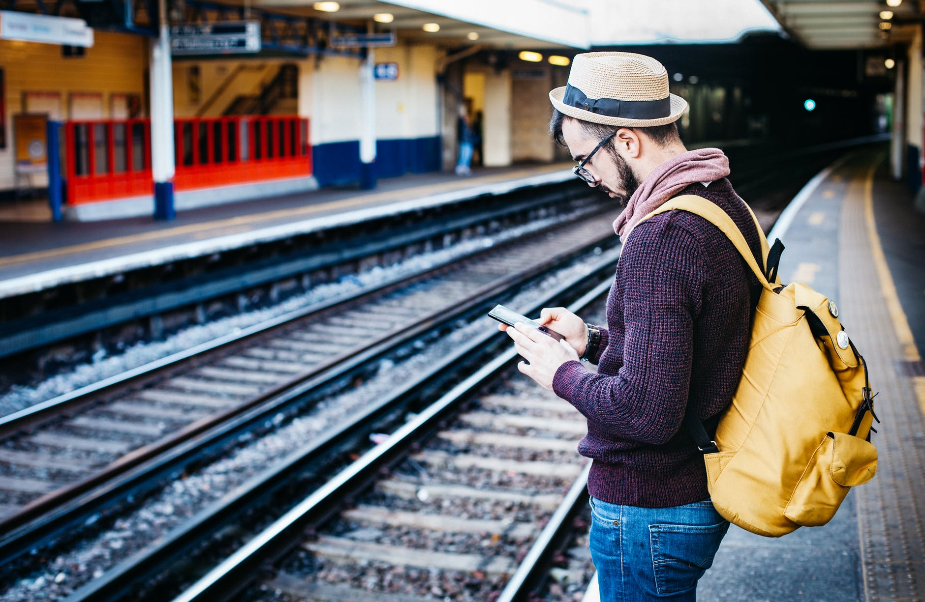man looking at his phone on a train platform