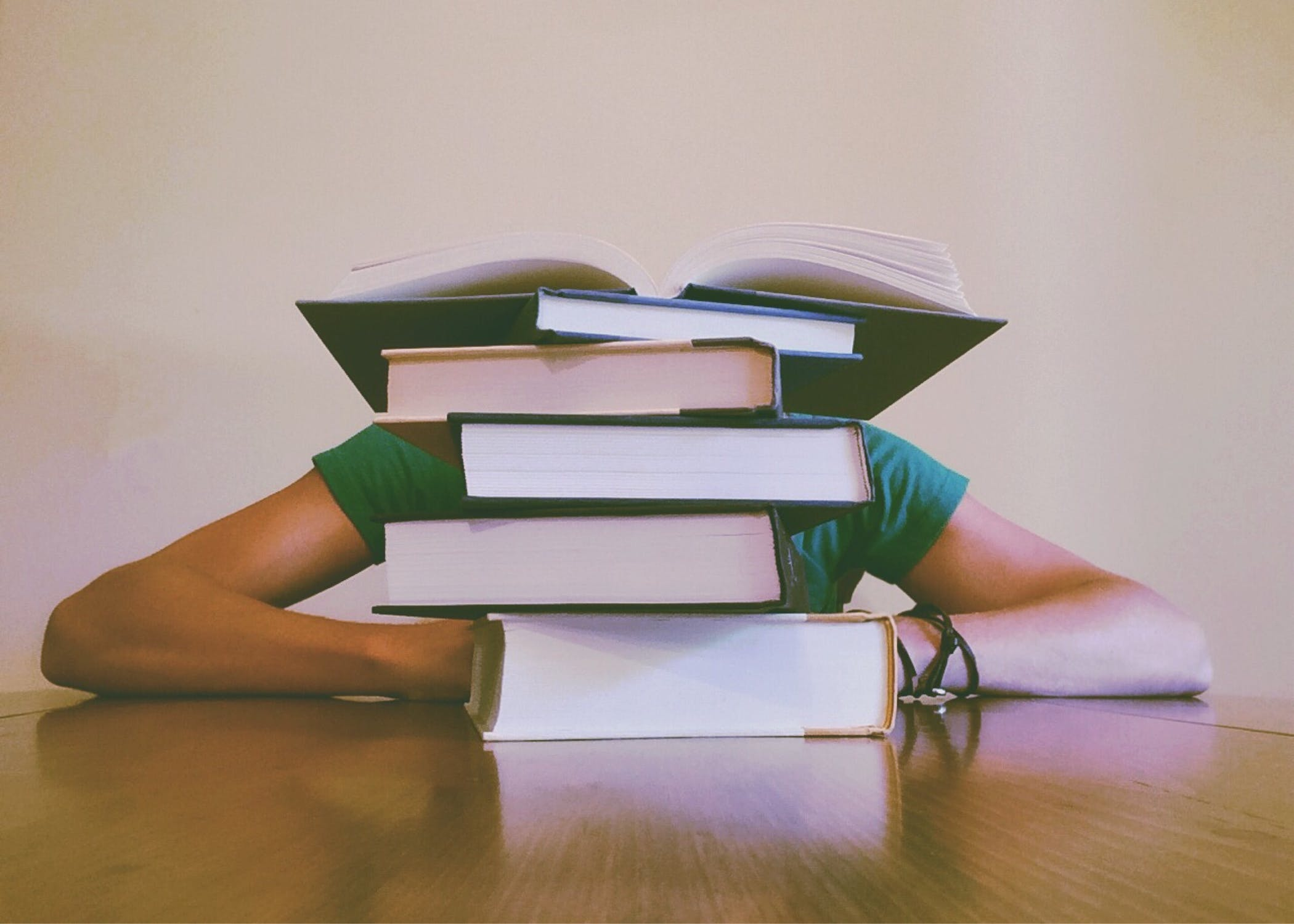 student asleep behind books