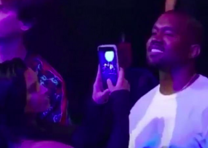 Kanye West and Kim Kardashian watching Rihanna