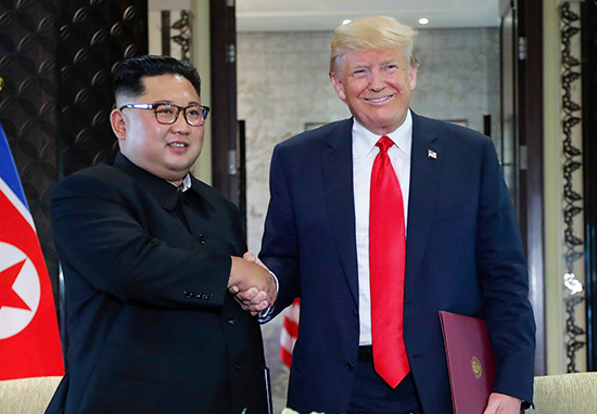 Kim Jong-un and Donald Trump shake hands