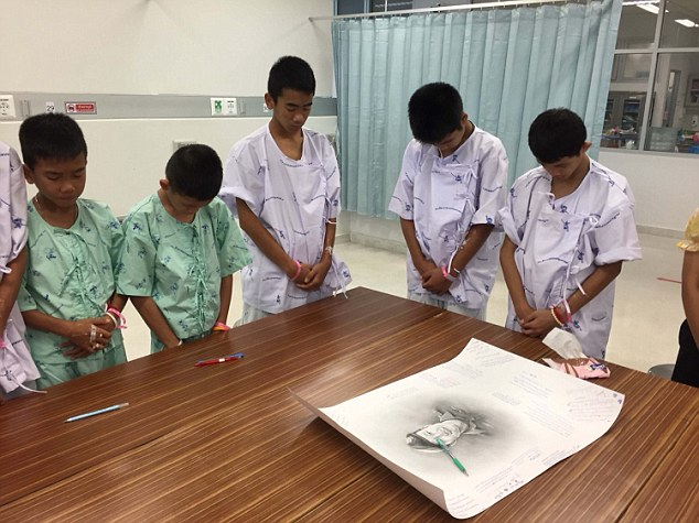 Thai boys bowing their heads to a photo of Saman Gunan