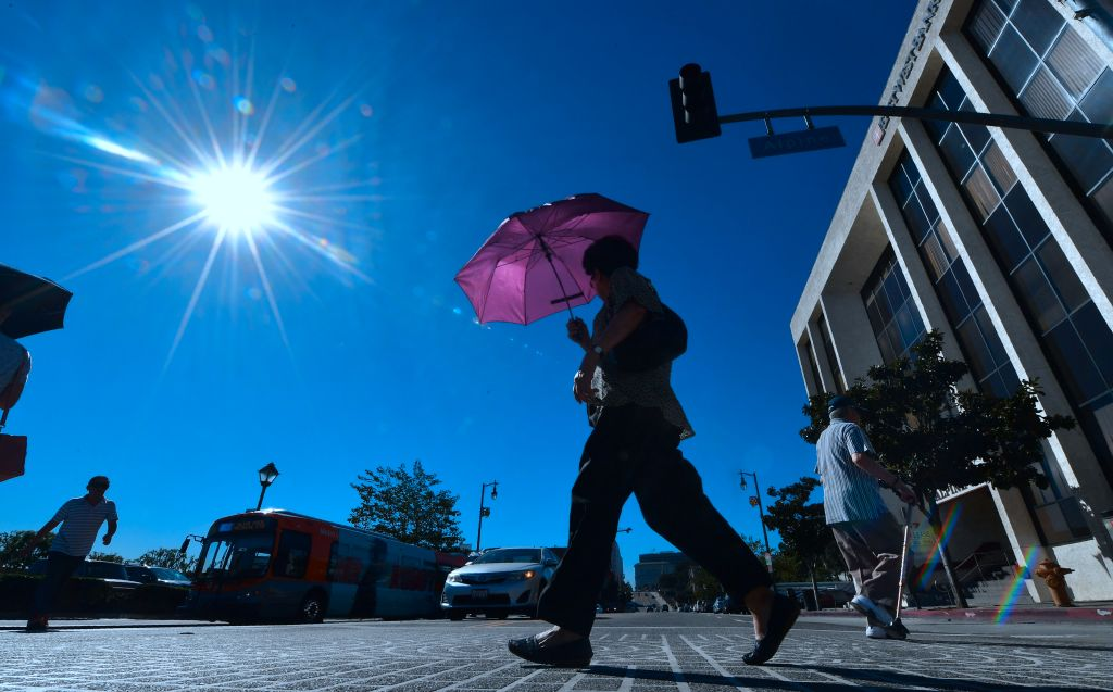 Man walks on LA street during heatwave which has broken heat records
